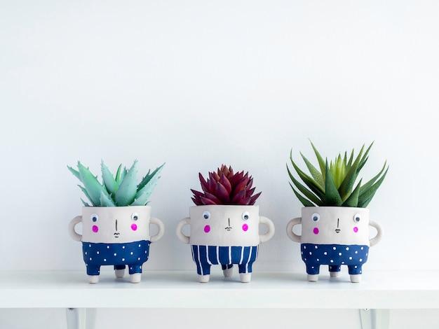 Niedliche keramische pflanzentöpfe mit grünen und roten sukkulenten auf weißem holzregal isoliert auf weißer wand mit kopierraum. drei kleine moderne diy-zementpflanzgefäße trendige dekoration.