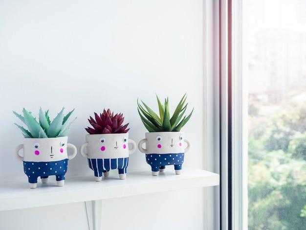 Niedliche keramische pflanzentöpfe mit grünen und roten sukkulenten auf weißem regal auf weißer wand in der nähe des glasfensters mit kopierraum. drei kleine moderne diy-zementpflanzgefäße trendige dekoration.
