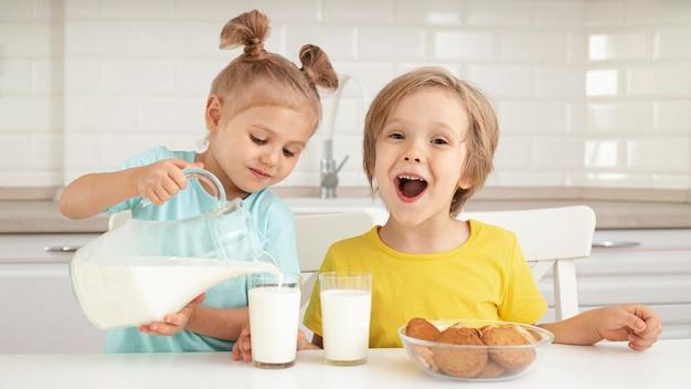 Niedliche kinder, die milch trinken