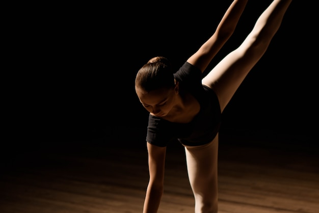 Niedliche kleine ballerina im dunklen ballettkostüm tanzt auf der bühne. kind in der tanzklasse. mädchen studiert ballett.