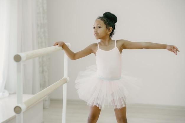 Niedliche kleine ballerina im rosa ballettkostüm. kind in spitzenschuhen tanzt im raum. kind im tanzkurs.