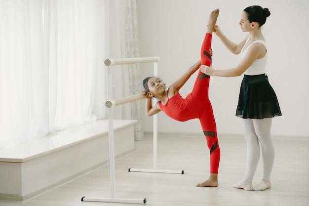 Niedliche kleine ballerina im roten sportanzug. kind tanzt im raum. kind im tanzkurs mit teatcher