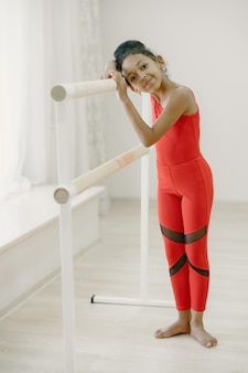 Niedliche kleine ballerina im roten spotanzug. kind tanzt im raum. kind im tanzkurs.