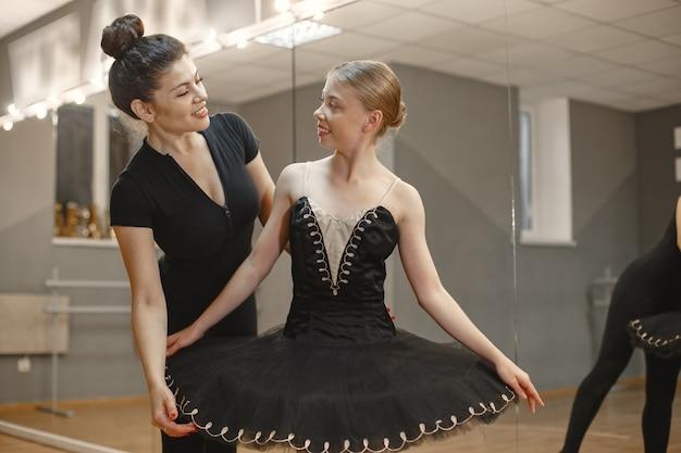 Niedliche kleine ballerina im schwarzen ballettkostüm. junge dame tanzt im raum. mädchen in der tanzklasse mit lehrer.