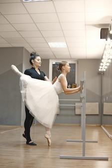 Niedliche kleine ballerina im weißen ballettkostüm. junge dame tanzt im raum. mädchen in der tanzklasse mit lehrer.