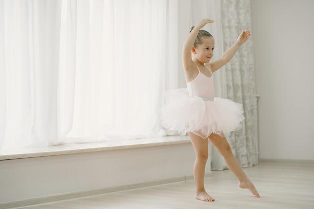 Niedliche kleine ballerinas im rosa ballettkostüm. kind in spitzenschuhen tanzt im raum. kind im tanzkurs.