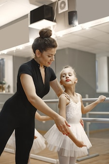 Niedliche kleine ballerinas im rosa ballettkostüm. kinder in spitzenschuhen tanzen im raum. kind im tanzkurs mit lehrer.