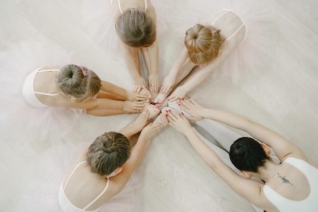 Niedliche kleine ballerinas im rosa ballettkostüm. kinder in spitzenschuhen tanzen im raum. kind im tanzkurs mit teatcher.