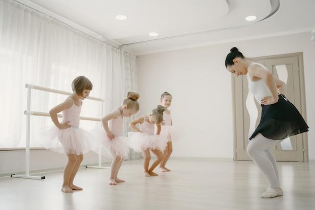 Niedliche kleine ballerinas im rosa ballettkostüm. kinder in spitzenschuhen tanzen im raum