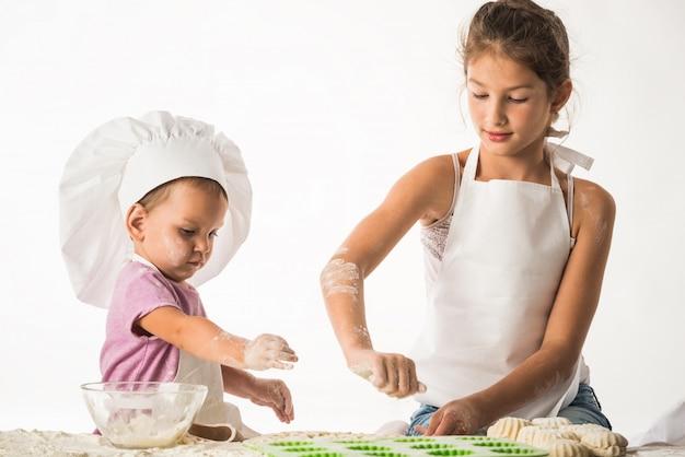 Niedliche kleine kinder bruder und schwester kochen
