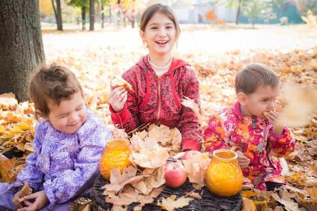 Niedliche kleine kinder gehen in den park und frühstücken, während sie auf gelben ahornblättern sitzen