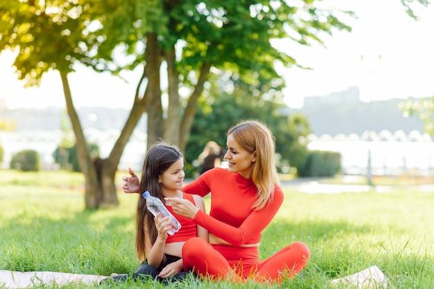Niedliche kleine tochter und mutter trainieren, fitness, yoga im morgenpark