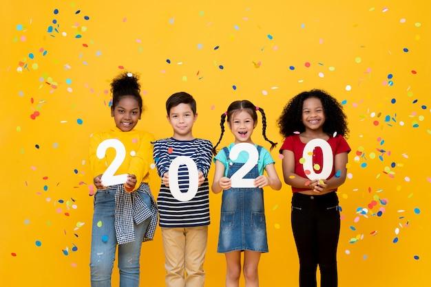 Niedliche lächelnde gemischte rassenkinder, die zahlen 2020 zeigen, die neues jahr feiern
