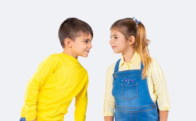 Niedliche lächelnde kinder schauen einander in den lässigen kleidern auf einem weißen hintergrund in die augen.