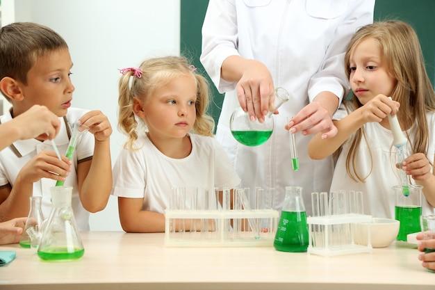 Niedliche schüler mit lehrer, der im chemieunterricht biochemieforschung betreibt