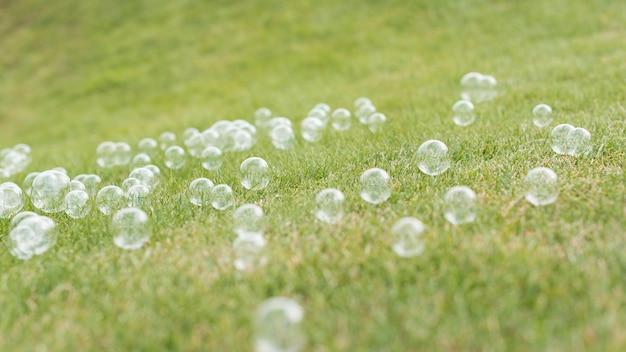 Niedliche seifenblasen der vorderansicht auf gras