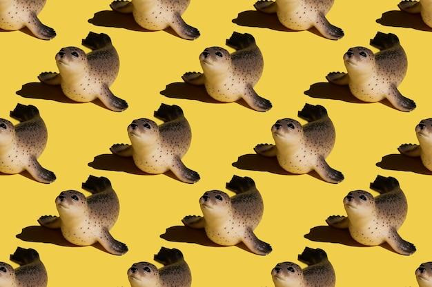 Niedliche spielzeug-pelzrobbe auf einem leuchtend gelben, nahtlosen muster. design für stoff, textil, dekor.