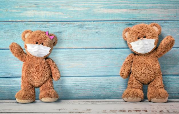 Niedliche teddybären, die hinter der maske lächeln, haben ein glückliches gesicht für soziales distanzierungskonzept. mit kopierraum.