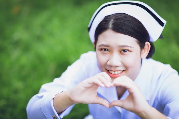 Niedliche thailändische asiatische krankenschwester einheitliches nahaufnahmelächeln mit handherzform für liebesanteil und pflegekonzept für menschen.