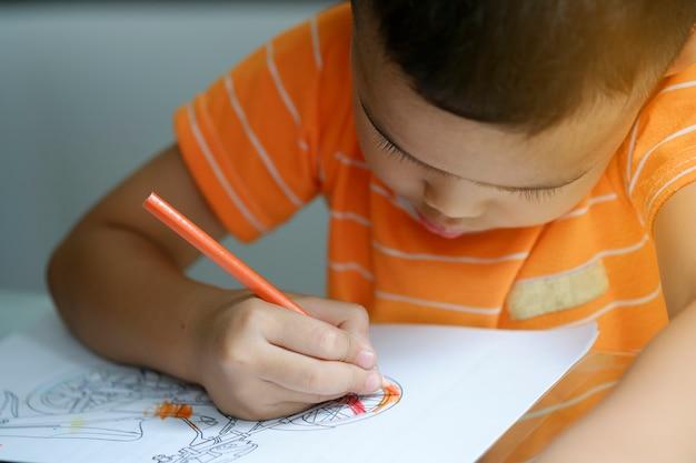 Niedlichen jungen zeichnung mit farbstiften, kind lernen konzept