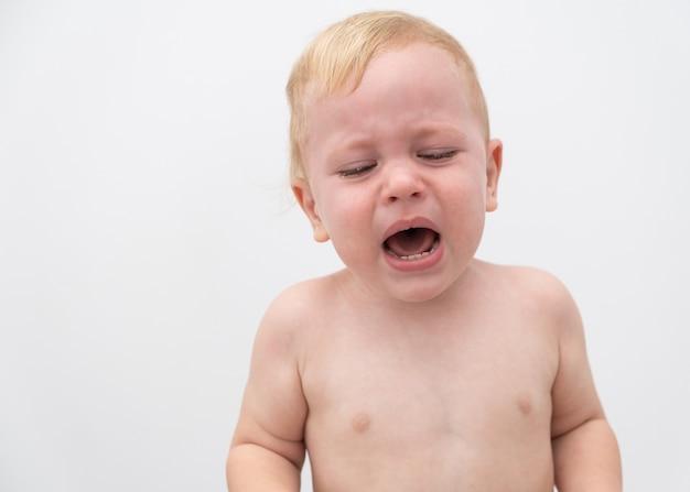 Niedlicher blonder babykleinkindjunge, der auf weißer wand weint
