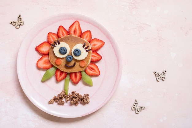 Niedlicher blumenpfannkuchen mit beeren für kinderfrühstück