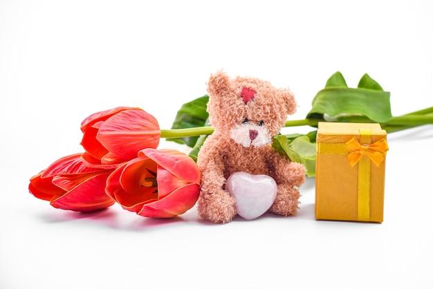 Niedlicher brauner teddybär, strauß roter tulpen, geschenkbox, liebes- oder romantikkonzept, angenommenes geschenk