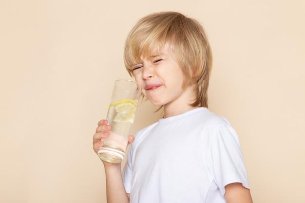 Niedlicher entzückender trinkender zitronensaft des kleinen kindes im weißen t-shirt auf rosa wand