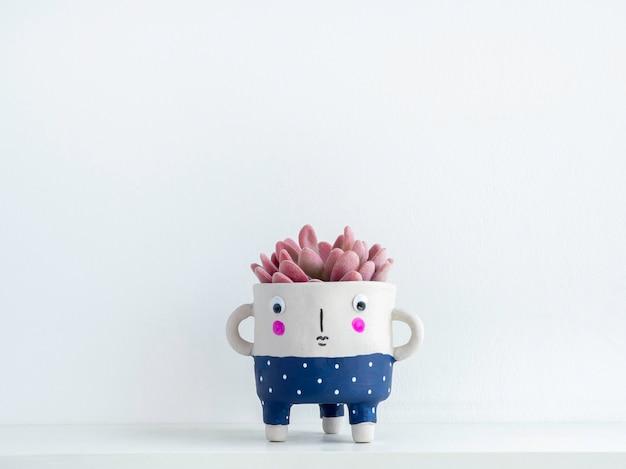 Niedlicher keramischer pflanzentopf mit rosafarbener sukkulente auf weißem holzregal isoliert auf weißer wand mit kopierraum. kleine moderne diy-zementpflanzer trendige dekoration.