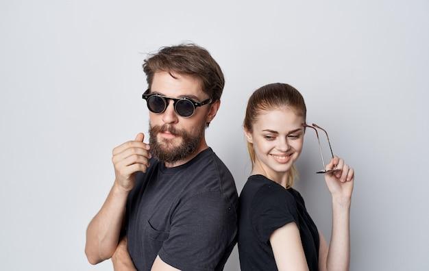 Niedlicher mann und frau tragen sonnenbrille schwarze t-shirts lebensstil beschnitten ansicht studio kommunikation
