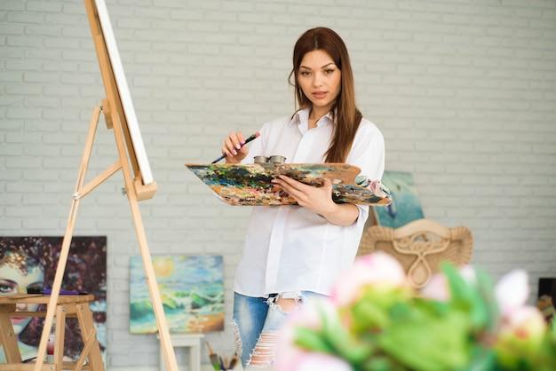 Niedlicher schöner mädchenkünstler, der ein bild auf einer leinwand auf einem gestell malt. studio weißer hintergrund. lange haare, brünette. hält bunte pinsel und palette.