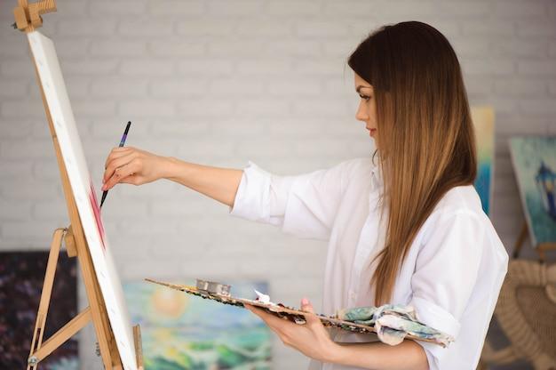 Niedlicher schöner mädchenkünstler, der ein bild auf einer leinwand auf einem gestell malt.