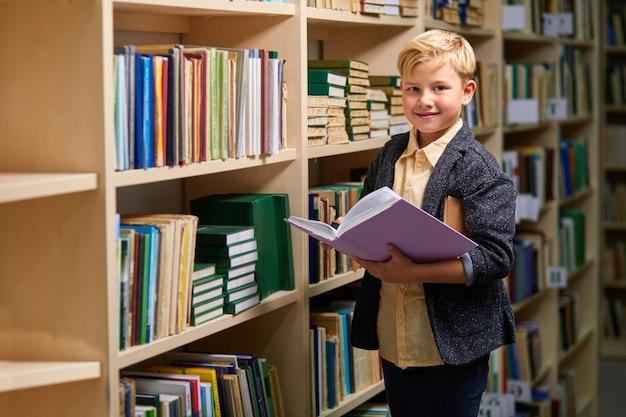 Niedlicher schuljunge, der lächelt, während er ein buch in der bibliothek liest, stehen und kamera betrachten