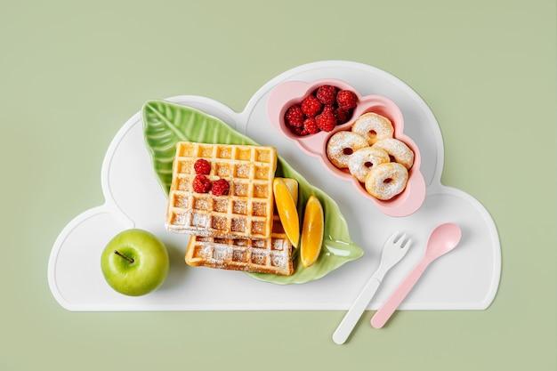 Niedlicher teller in form eines tropischen blattes mit waffeln und früchten. essensidee für kinder. kinderfrühstück.