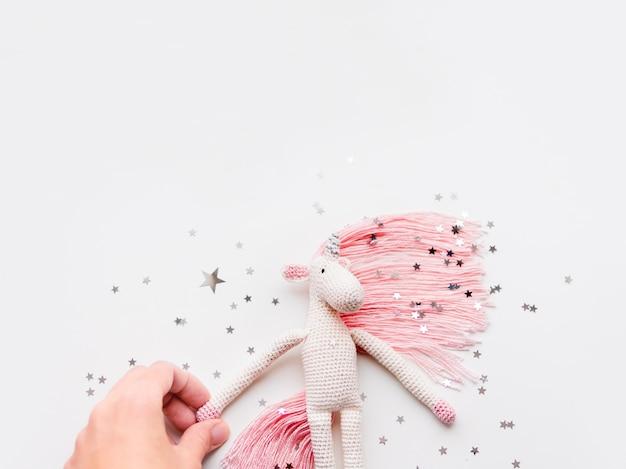 Niedliches feenhaftes einhorn mit einer rosa mähne und einem schwanz aus fäden.