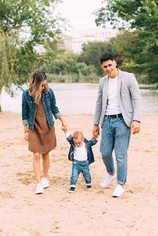 Niedliches foto der familie, die ihre hände hält und nahe einem see auf sand geht