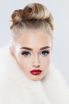 Niedliches gesicht. frau mit make-up, modischer frisur und weißem fell