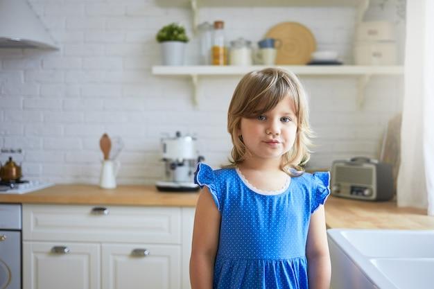 Niedlichkeit, süßes zartes alter und innenarchitekturkonzept. porträt des niedlichen entzückenden weiblichen kindes im blauen kleid schmollende lippen, missfallen gesichtsausdruck, posierend in der küche,