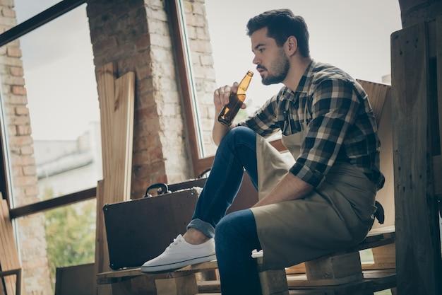 Niedrig unter winkelansicht ernsthafter selbstbewusster nachdenklicher mann, der bier aus der flasche trinkt und nachdenklich über seine nächste bestellung nachdenkt