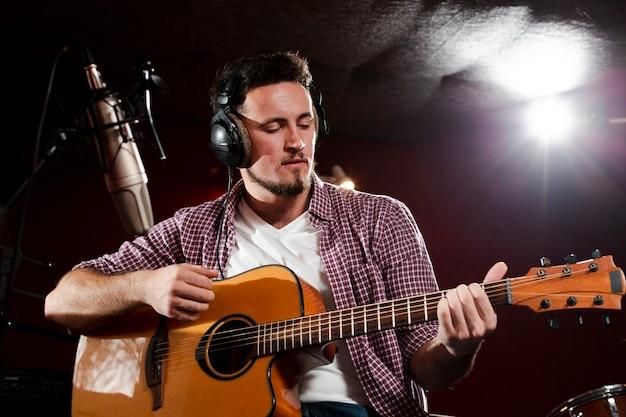 Niedrige ansicht schoss von einem mann, der gitarre spielt und kopfhörer trägt