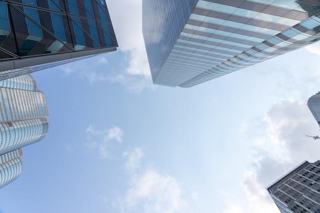 Niedrige ansicht von wolkenkratzern mit blauem himmel und wolken und modernes geschäft des bürogebäudes