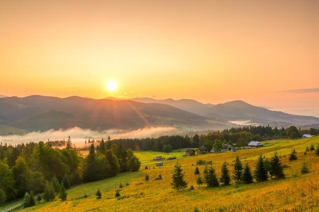 Niedrige berge und bewaldetes tal. sommer. mehrere bauernhäuser. morgennebel im tal. die sonne geht am wolkenlosen himmel auf