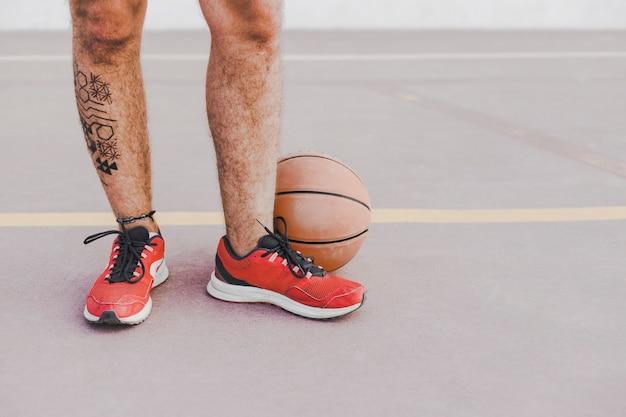 Niedrige schnittansicht der füße eines mannes mit basketball