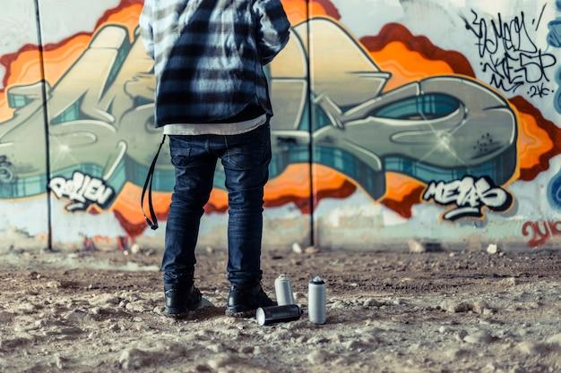 Niedrige schnittansicht des künstlers, der nahe spraydose vor graffiti auf wand steht