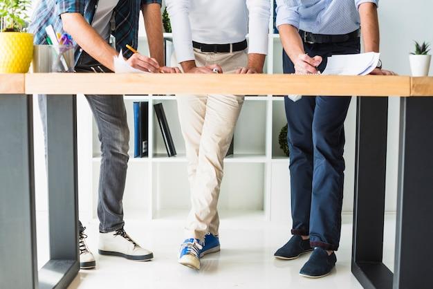 Niedrige schnittansicht des männlichen architekten drei, der im büro arbeitet
