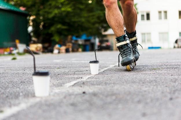 Niedrige schnittansicht des rollerskater-slaloms durch entsorgungstasse