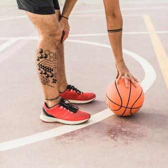 Niedrige schnittansicht eines mannes, der vor gericht basketball aufhebt