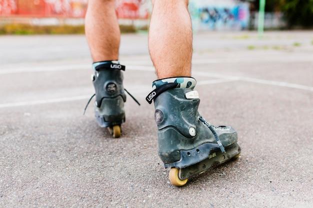 Niedrige schnittansicht eines mannes fuß rollerskating im skate park