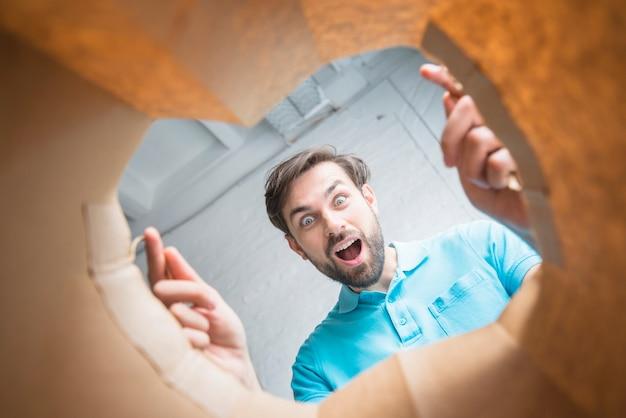 Niedrige schnittansicht eines überraschten mannes, der innere papiertüte schaut
