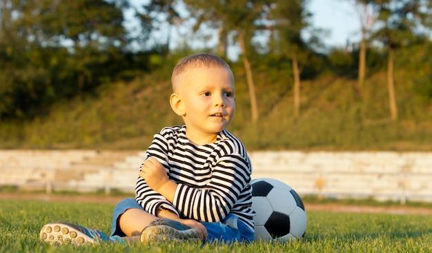 Niedrige winkel-nahaufnahmeansicht eines jungen, der mit seinem fußball auf grünem gras im abendsonnenschein sitzt